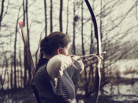 중세 아처 여자, 그녀는 chainmail 착용 하 고 활과 화살, 우울한 숲, 이미지 처리를 사용합니다.