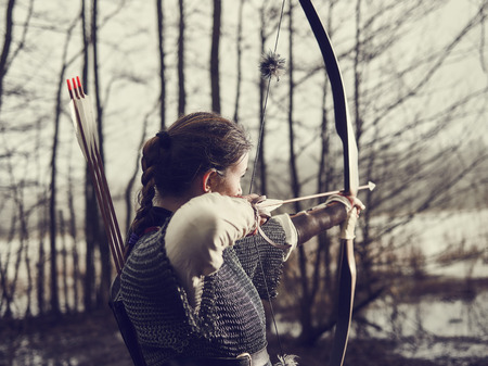 Medieval archer woman, she wearing a chainmail and use a bow and arrow, gloomy forest, cross-processed image. Stockfoto