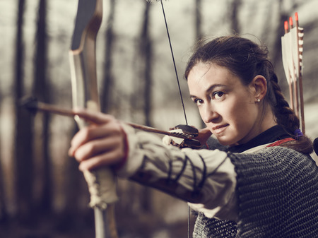 warrior girl: Medieval archer woman, she wearing a chainmail and use a bow and arrow, gloomy forest, cross-processed image. Stock Photo
