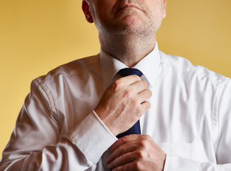 tighten: Close up, male wearing white shirt and blue tie, he tighten the tie knot, yellow background