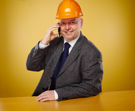 crash helmet: Working male engineer in office, he wearing a white shirt and tie and coat, head he wears a orange hard hat Stock Photo