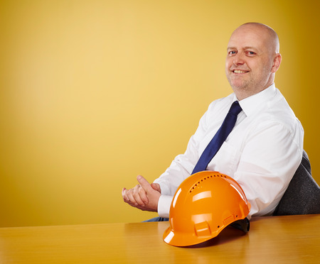 crash helmet: Male engineer in office, he wearing a white shirt and tie, the orange hard hat is on the table