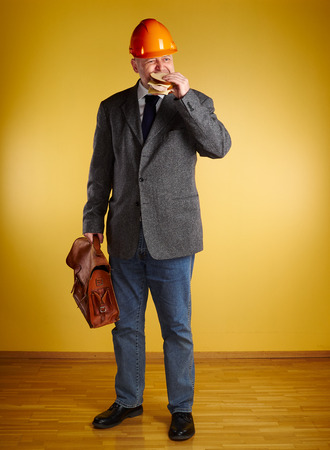 hurried: Male engineer in room, he eats sandwich and holds old leather briefcase, parquet floor and yellow wall