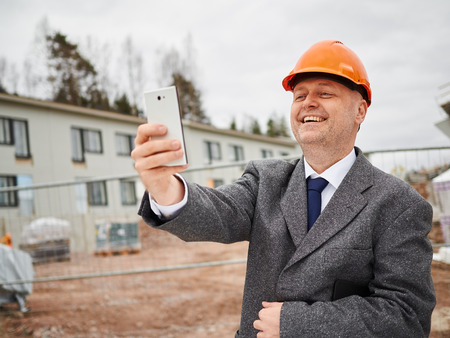 crash helmet: Male engineer take selfie, he wearing the suit and the hard hat, house construction site on background