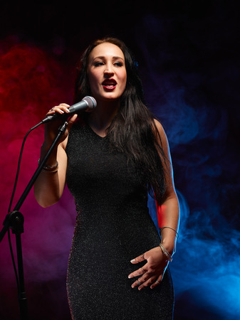 Beautiful woman sings, smoky stage on background Stock Photo