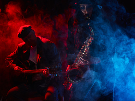 Saxophonist, beautiful young woman, smoky stage and guitarist on background