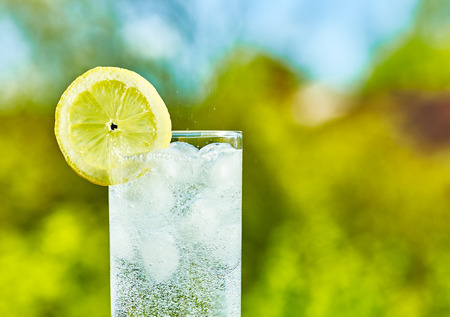 Sparkling water and lemon slice on glass with an ice, sunny day - narrow focus on middle of the glass Stockfoto