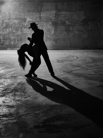black shadow: Man and woman dancing urban dancing theme concrete building surroundings black and white image Stock Photo