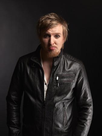 rocker: Male rocker wearing black leather jacket, dark background and studio shot
