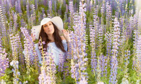 summery: Fashionable young woman wearing a white hat and shirt, summery meadow