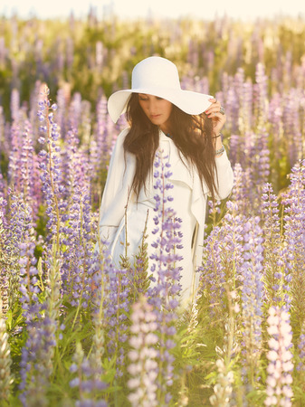 summery: Fashionable young woman wearing a white hat and jacket, summery meadow
