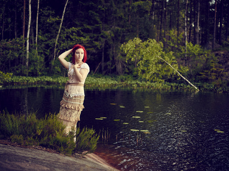 carroty: Attractive young woman wearing a dress and she standing beside waterline, lake on background