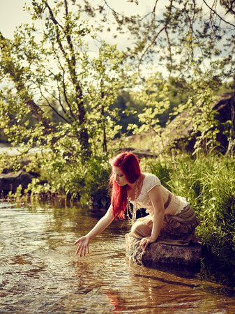 carroty: Attractive young woman sits on the rock and she dreams, summer day on the lake