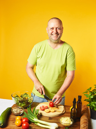 Fresh salad ingredients on the table, middle-aged man cut tomatoes -  yellow background Stock Photo