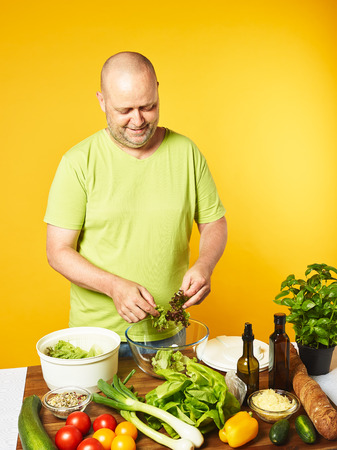Fresh salad ingredients on the table, middle-aged man cook salad and used salad spin dryer -  copy space and yellow background Stock Photo