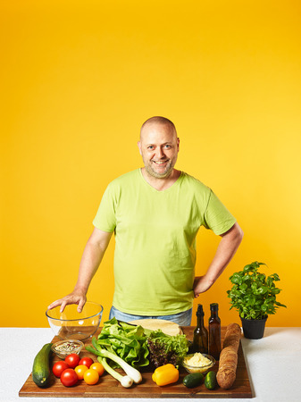 Fresh salad ingredients on the table, middle-aged man -  copy space and yellow background Stock Photo