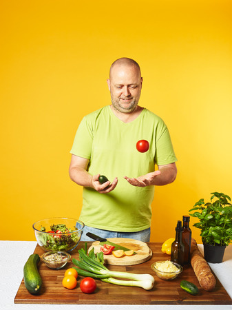 Fresh salad ingredients on the table, middle-aged man throws vegetables into the air  -  copy space and yellow background Stock Photo