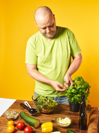 adds: Fresh salad ingredients on the table, middle-aged man adds basil leaves  salad -  yellow background