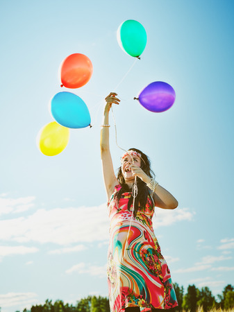 Beautiful pregnant young woman feeling lovely and relax outdoors and she plays with a balloons photo