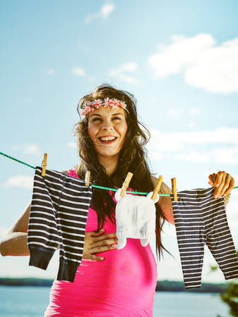 Beautiful pregnant young woman feeling lovely, children clothes on clothesline photo