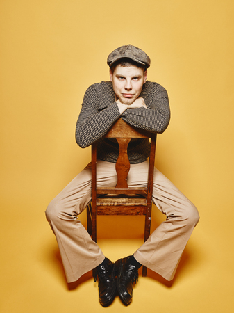 sits on a chair: Expressive man sits on the chair and 70s look theme, yellow background Stock Photo