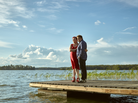 boat dock: Lovely couple standing on the boat dock, warm summer evening light