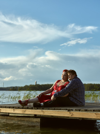 boat dock: Lovely couple sits on the boat dock, warm summer evening light