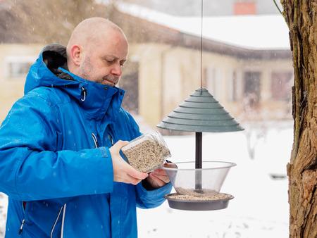 bird feeder: Winter day and snowfall, man fills a bird feeder, horizon format Stock Photo