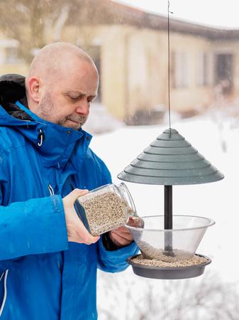 fills: Winter day and snowfall, man fills a bird feeder, vertical format
