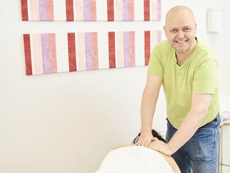 Massage, professional masseur and a woman customer Stock Photo