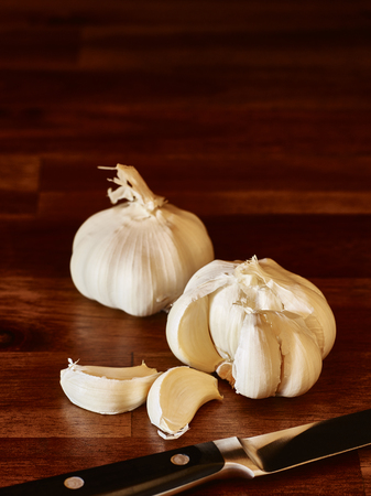 Garlic and knife on the wooden cutting board, vertical image Stock Photo