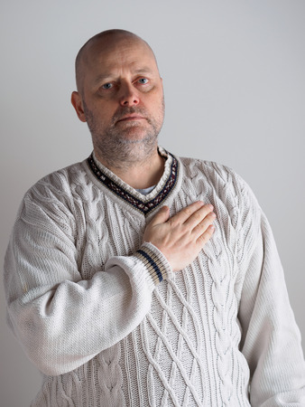 testify: Portrait, casual looking caucasian male wearing a white pullover, right hand over heart and he looks toward the camera Stock Photo