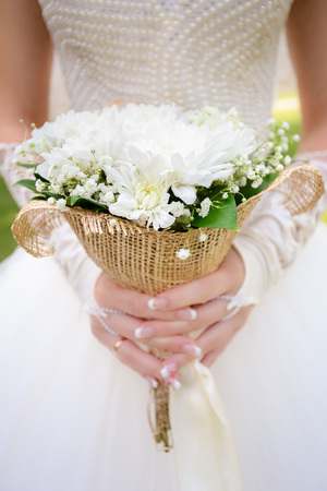 dreaminess: Wedding bouquet on the background of the bride in a white dress