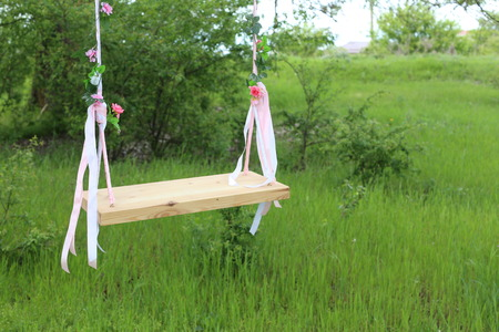 chain swing ride: Empty swing in nature, blurred green background