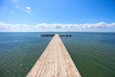 over the edge: pier stretching into the sea in Sunny weather, blue sky with clouds