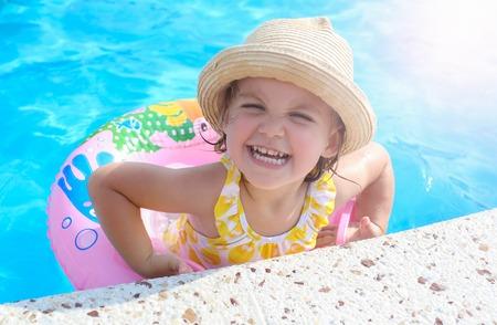 Gelukkig meisje spelen met kleurrijke opblaasbare ring in het buitenzwembad. Kinderen leren zwemmen. Kinderen waterspelen. Familie strandvakantie.