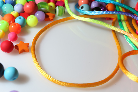 colorful beads and thread on white background