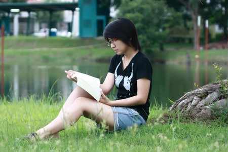 beautiful asia woman reading in the park photo
