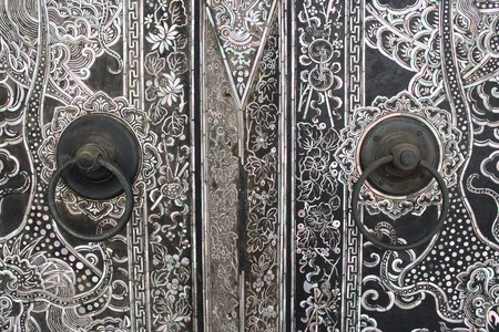 Native Thai style wood carving on door at temple photo