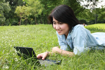 A smiling young girl with laptop outdoors in the park photo