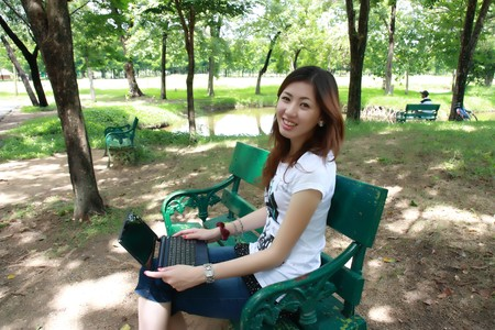 Young pretty woman with laptop on the bench in a park photo