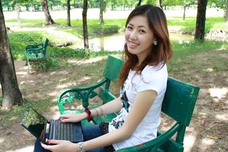 Young pretty woman with laptop on the bench in a park Stock Photo - 7889651