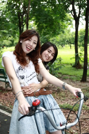 old people having fun: Two friends on bikes outdoors smiling in the park