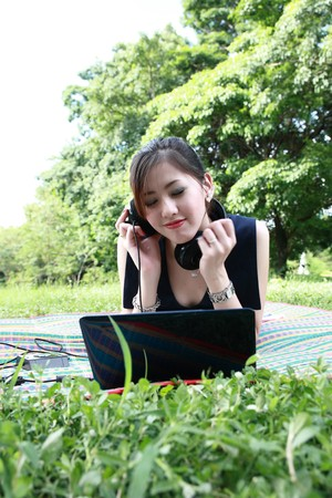 attractive Asian woman is outdoors with laptop computer photo