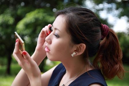 Beautiful woman applying colorful eye makeup photo