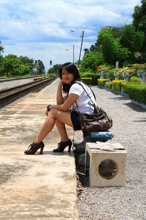 Young traveling woman with her suitcases on the railway tracks photo