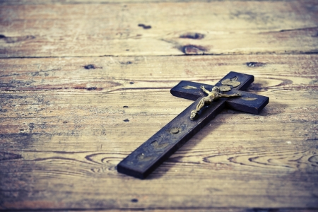 Beautiful old cross with jesus on the old wooden floor photo