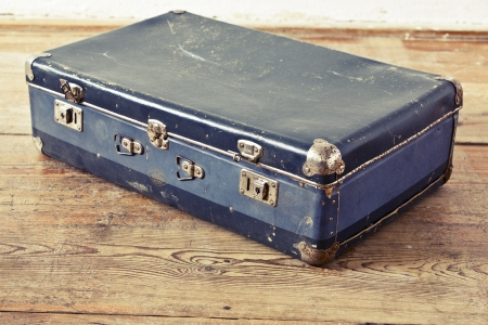 Old blue suitcase on the wooden vintage floor photo