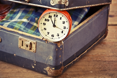 Old suitcase with old alarm clock and old shirt photo