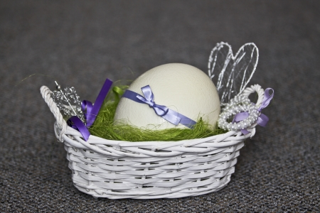 Big easter ostrich egg in the white basket photo